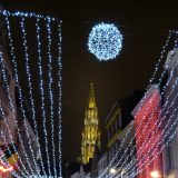 The spire of the Brussels Town Hall looms over a street at night.