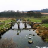Hikers cross a stone bridge dating to the 1300's in Devon's rugged moorlands.