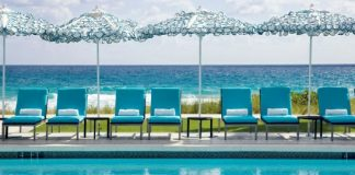 Relax poolside under the umbrellas at Boca Beach Club, a Waldorf-Astoria Resort.