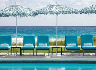 Relax poolside under the umbrellas at Boca Beach Club, a Waldorf-Astoria Resort.