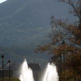 Visitors at the Nagasaki Peace Park are silhouetted against large fountains that symbolize world peace.