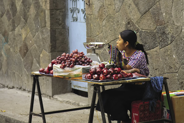 Woman in traditional attire selling fruit in Santiago Atitlan.
