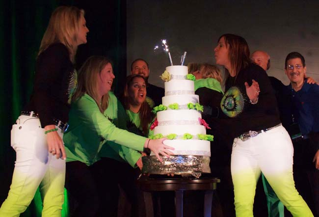 COO of Cruise Planners, Vicky Garcia, blows out the candles to celebrate the franchise company's 20th anniversary.