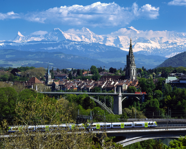 Kornhausbruecke, the Muenster, and the old town of the Capital of Switzerland, Bern with the Alps with Eiger, Moench and Jungfrau in the back. (Photo Courtesy of Switzerland Tourism. Photo by Christof Sonderegger.)
