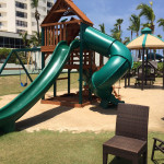 A playground for kids near the pool with a basketball court next to it at the Caribe Hilton Hotel.
