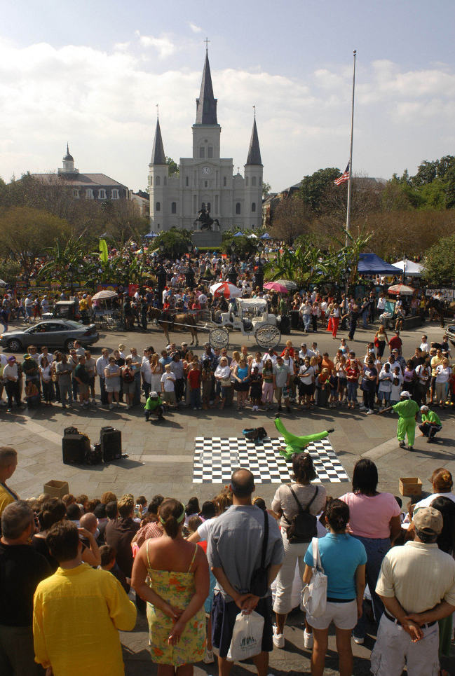 Visitors taking in a street performance in New Orleans with the cathedral in the background.