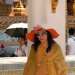 A woman in an elaborate sunhat more appropriate for the Kentucky Derby visits the Grand Palace.