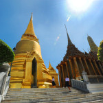Visitors dwarfed by the golden stupa of the Grand Palace.
