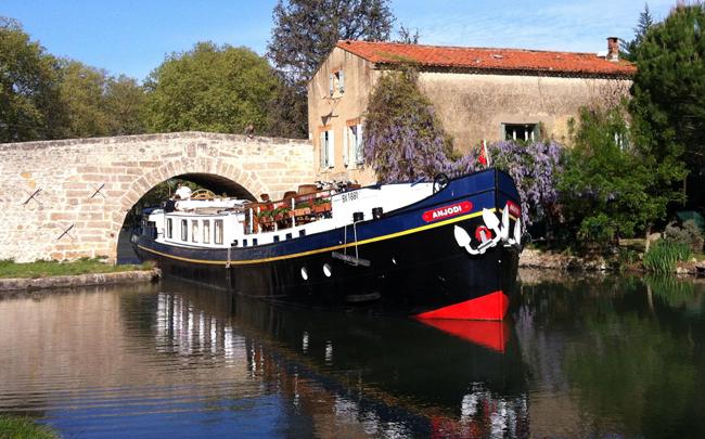 The Anjodi cruising under a bridge in France.