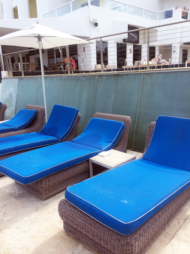 Poolside lounge chairs and cascading waterfall wall at Marriott Stanton South Beach.