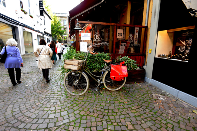 Bicycles, cobbled streets, sidewalk cafes and shop windows displaying upscale items present a typical Antwerp scene near the Opera House.