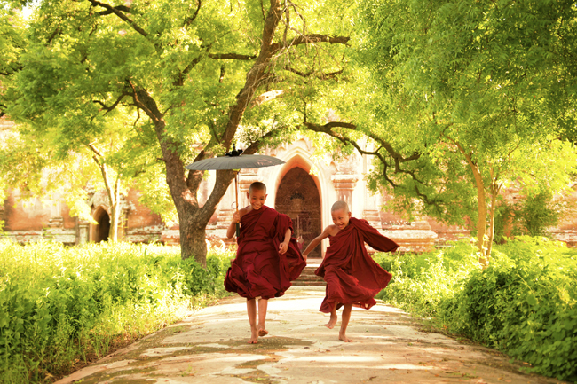 Two little monks running in Myanmar.