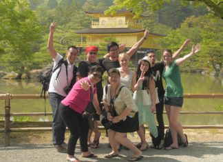 A group of traveler with Super Value Tours in front of the Golden Pavillion.