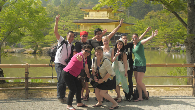 A group of travelers with Super Value Tours in front of the Golden Pavillion.