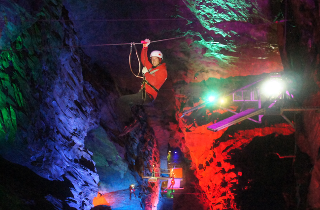 A guest glides through Zip World Caverns zip lines.