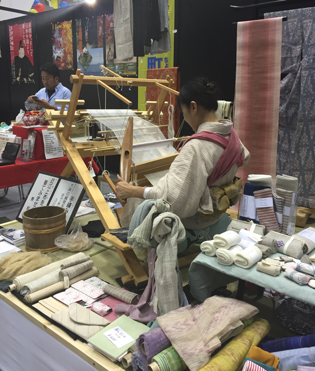 Viewing traditional crafts in the making at JATA Tourism EXPO Japan.