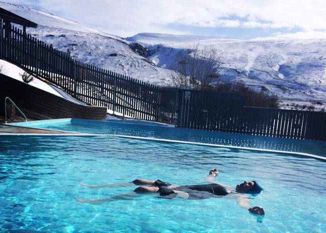 Outdoor thermal pools and hot tubs at the eco-friendly Hotel Husafell in Iceland.