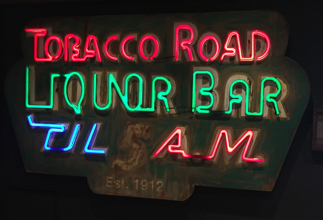 The neon sign outside of Norwegian Escape'sTobacco Road bar.