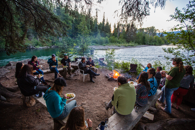 Guestsenjoying a meal by the campfire atBear Claw Lodge in Canada'sKispiox Valley.