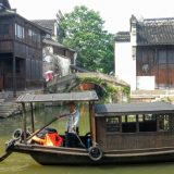 A local floating along the river in the ancient water town of Wuzhen.