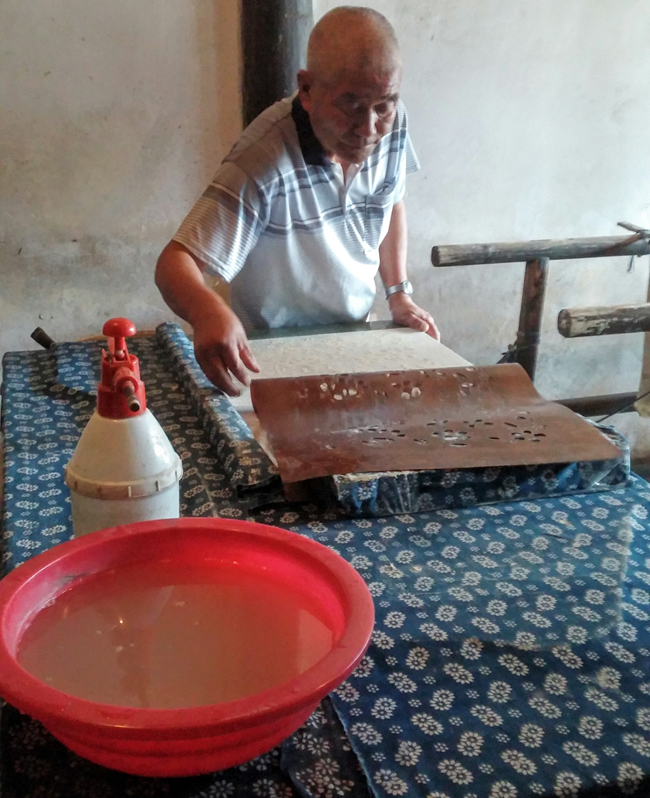 A local resident practicing the traditional method of dying blue silk at the Indigo Fabric shop.