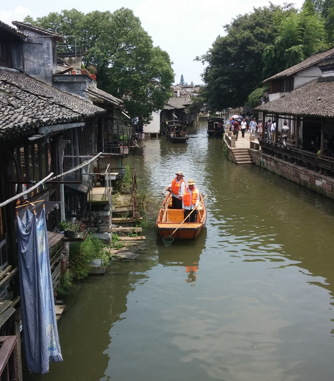 Locals boating on the jade-hued river in Wuzhen, an ancient Chinese water town located on the banks of the Grand Canal.