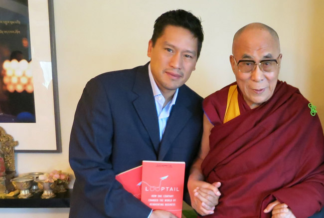 "G Adventures founder Bruce Poon Tip shares an inspiring moment with His Holiness The Dalai Lama, during the publication of Bruce's New York Times Bestselling memoir, ""Looptail"" in 2013. (Photo credit: G Adventures, Inc.)"
