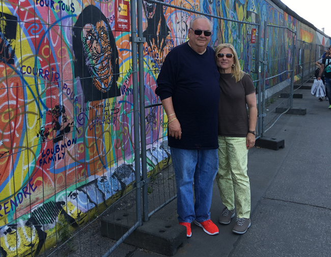 Lisa and her husband, Andre Perlo, visiting the Berlin Wall.