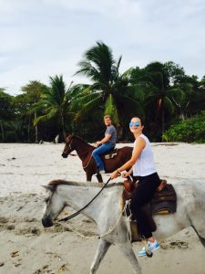 Jared horseback riding on the beach with his wife.