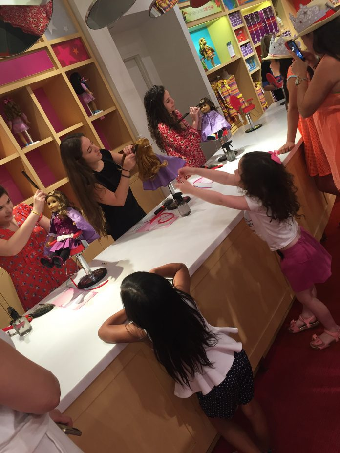 Moms and daughters watch as their dolls get a makeover at The American Girl doll store.
