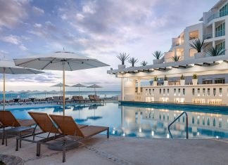 Guests at Playacar Palace can relax by the pool while looking out at the ocean.