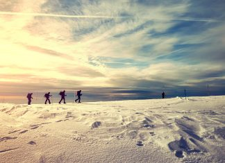 Winter landscape with travelers silhouettes at sunset.