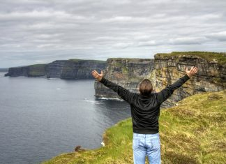 A traveler taking in the Cliffs of Moher on the Ireland Singles Hopper itinerary. (Photo courtesy of Tenon Tours.)