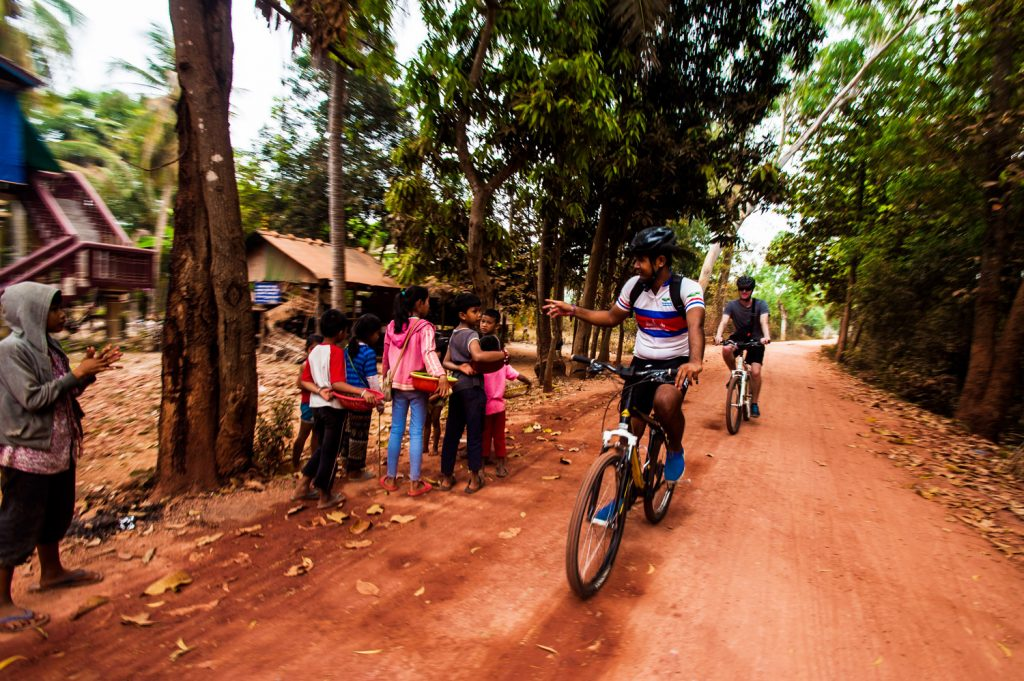 Bikers riding through local villages. (Photo courtesy of Grasshopper Adventures.)