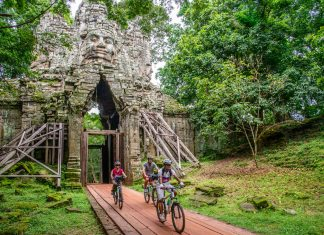 Travelers biking through Angkor. (Photo courtesy of Grasshopper Adventures.)