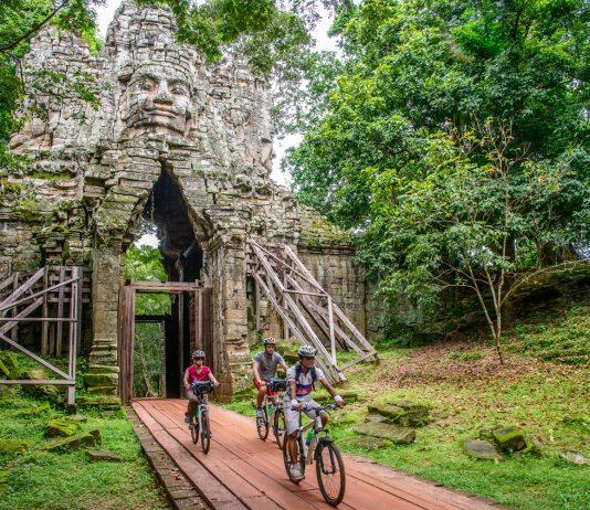 Travelers biking through Angkor. (Photo courtesy of Grasshopper Adventures.)