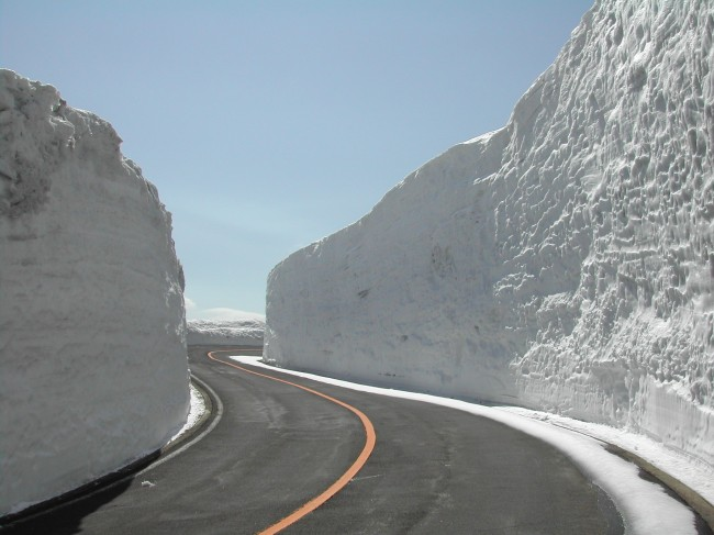 The Zao Echo Line roadway leading to the volcanic crater lake with snow on each side.